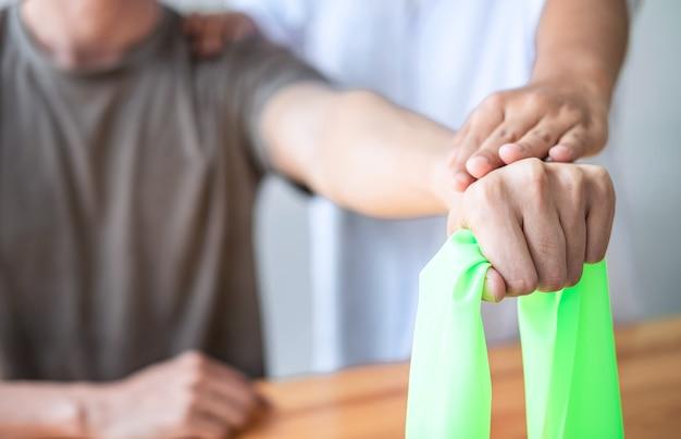 의사나 물리치료사는 운동선수 남성 환자의 부상당한 팔을 치료하고 스트레칭과 운동을 하고, 병원에서 재활 치료 통증을 하고 있습니다.