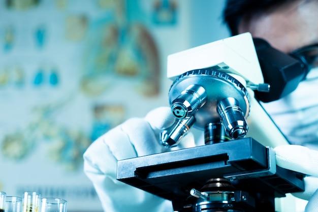 Врач или ученый носят медицинскую маску и смотрят в микроскоп, работая над медицинскими исследованиями в научной лаборатории
