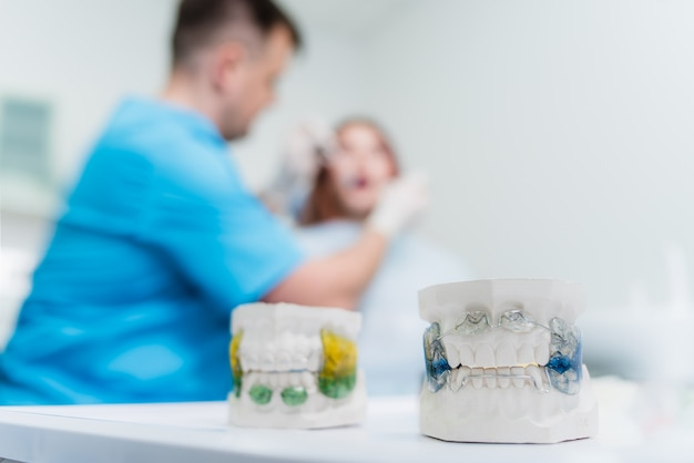 Doctor orthodontist examines the oral cavity of the patient
