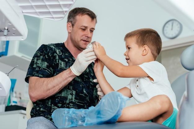 치과 교정 의사는 아이에게 치아를 관리하고 위생을 유지하는 방법을 알려줍니다