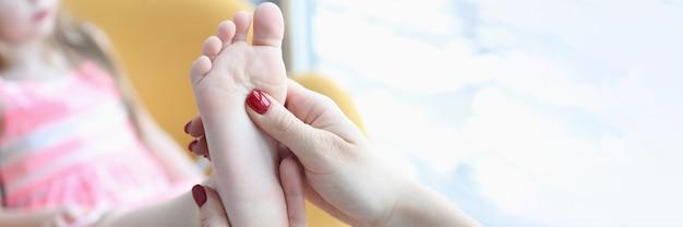 어린 소녀 근접 촬영의 발을 검사 하는 의사 정형 외과 의사