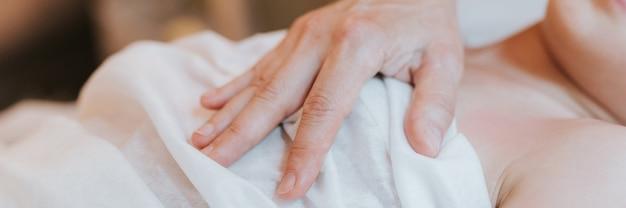 整骨医の手は、8歳の子供の女の子のために生理学的および感情的な治療を行います。小児オステオパシー治療セッション。代替医療。子供の健康の世話をします。バナー
