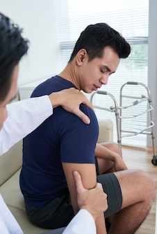 Doctor palpating patients shoulder at clinic