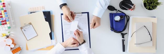 의사는 의사 개념에 작업 테이블 약속에서 환자에게 명함을 전달합니다.