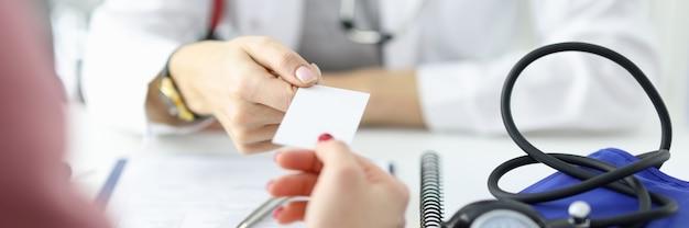 의사는 의료 사무실 의료 센터에서 환자에게 명함을 전달합니다.