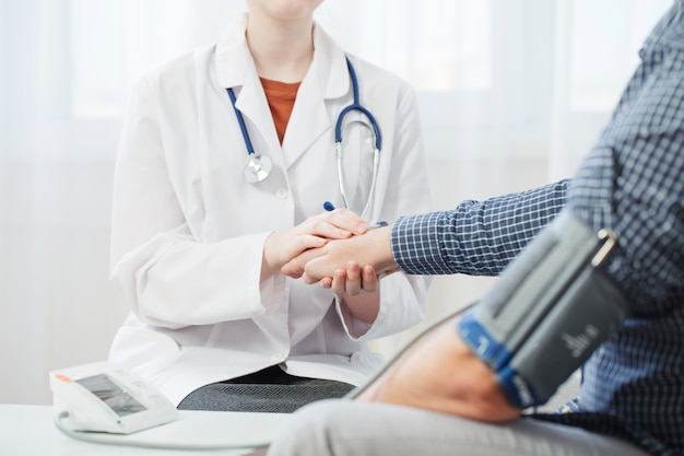 Doctor and patient measuring blood pressure, healthcare, hospital and medicine concept
