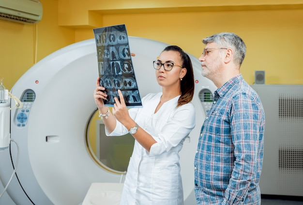Doctor and patient in the room of computed tomography at hospital.