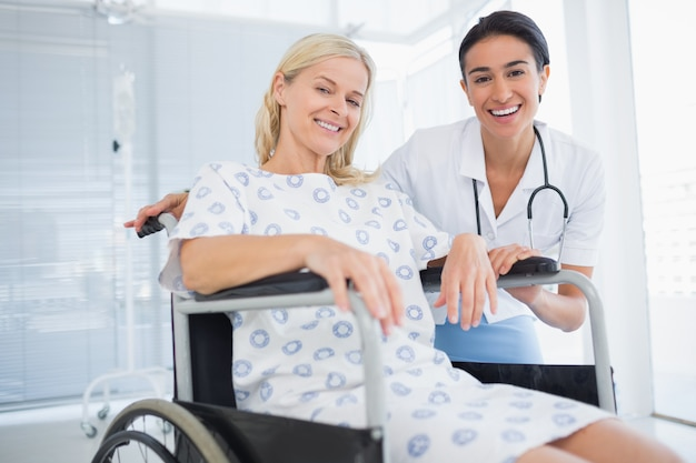 Doctor and patient in wheelchair smiling at camera
