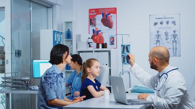 Medico e pazienti che guardano i raggi x seduti in studio medico. medico specialista in medicina che fornisce consulenza sui servizi di assistenza sanitaria, trattamento radiografico nell'armadio ospedaliero della clinica
