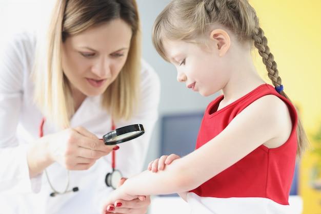 Врач-педиатр исследует сыпь на коже руки маленькой девочки с помощью увеличительного стекла