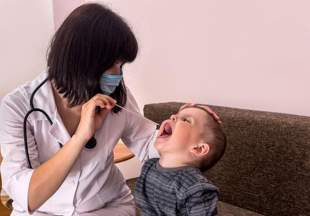 小さな男の子の喉を調べる小児科医