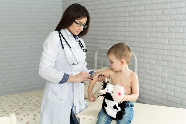 아이에게 팔에 근육 주사를 주는 의사 소아과 의사