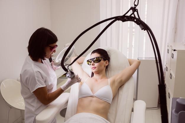 女性患者の皮膚にレーザー脱毛を行う医師