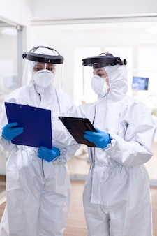 Covid-19로 전 세계적으로 유행하는 동안 개인 보호복을 입은 의사. 안전 예방 조치로 코로나바이러스 감염에 대한 전문 장비를 착용한 의료 동료.