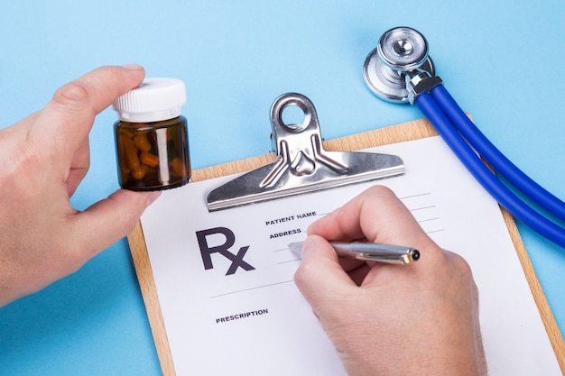 Doctor or pharmacist holding jar or bottle of pills in hand and writing prescription on a special form. medical costs and healthcare payment concept.
