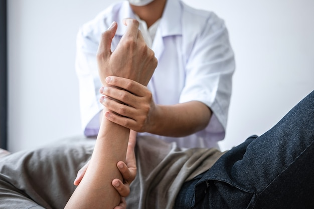 Doctor or physiotherapist working examining treating injured arm of athlete male patient, stretching and exercise, doing the rehabilitation therapy pain in clinic.