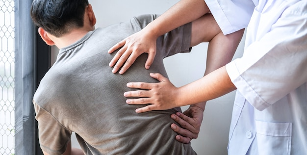 Doctor or physiotherapist working examining treating injured back of athlete male patient