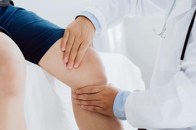 의사 물리치료사는 환자의 부상당한 무릎을 치료하는 일을 하고 있으며, 환자의 무릎에 손잡이를 사용하여 통증을 확인합니다.