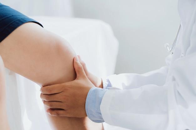 Врач-физиотерапевт работает, исследуя лечение травмированного колена пациента, с помощью ручки к колену пациента, чтобы проверить наличие боли.