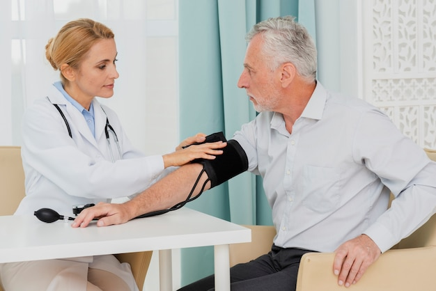 Doctor placing blood pressure cuff