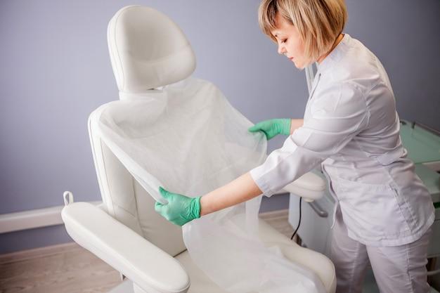椅子に使い捨ての布を置く医者