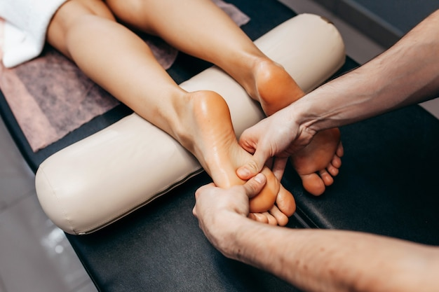 The doctor-podiatrist does an examination and massage of the patient's foot in the clinic.