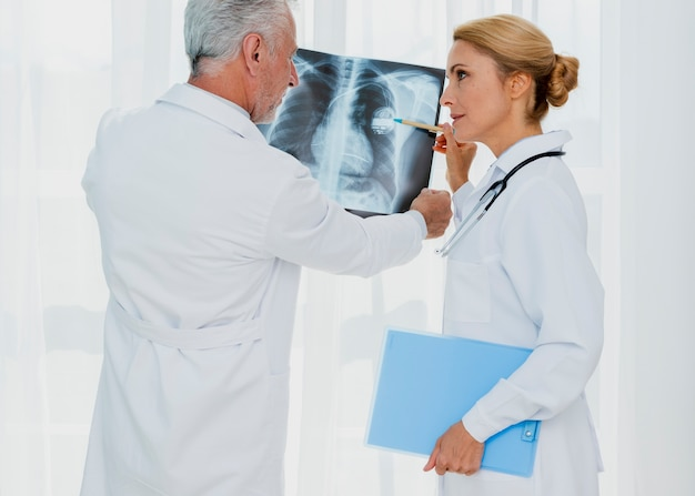 Доктор, указывая на кардиостимулятор на рентген