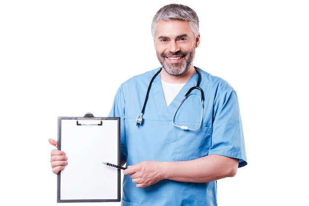 Doctor pointing clipboard. cheerful mature doctor looking at camera and smiling while pointing copy space on his clipboard and standing isolated on white