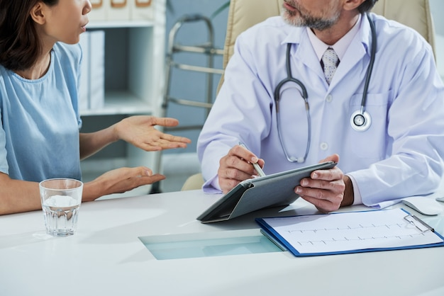 Doctor pointing at digital tablet screen while explaining something to the patient