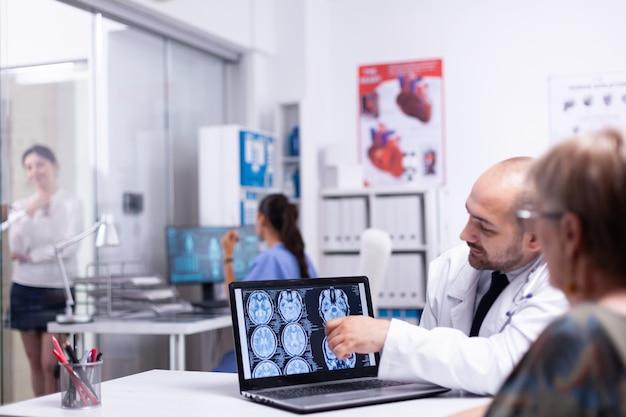 病院でラップトップを使用して高齢の患者と話しているデジタル脳x線を指している医師。医師を訪問している年配の女性は、治療を説明している医療従事者の健康上の苦情について話します。