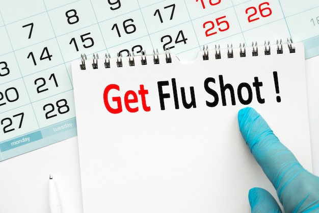 The doctor points to the text get flu shot, medical concept