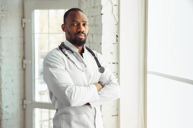 窓の近くの彼のキャビネットで自信を持ってポーズをとっている医者。患者との仕事中にアフリカ系アメリカ人の医師が、薬のレシピを説明します。流行中の健康と命を救うための毎日のハードワーク。