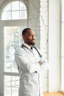 窓の近くのキャビネットで自信を持ってポーズをとる医師