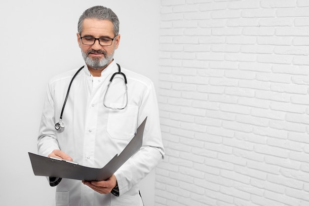 Doctor posing with folder and stethoscope.