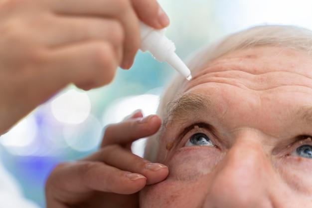 Доктор поливает глазные капли пациенту