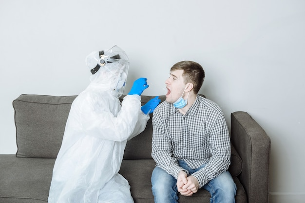 Doctor in ppe protective suit takes a swab test for a sample of coonavirus covid-19 virus from a patient