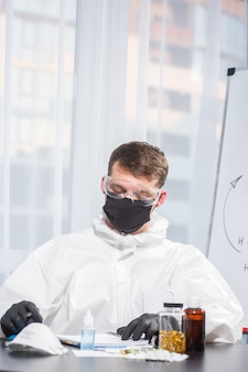 Doctor in ppe suit uniform calculates the virus formula. coronavirus outbreak. concept of covid-19 quarantine. doctor and medical care. personal protective equipment . stop virus.