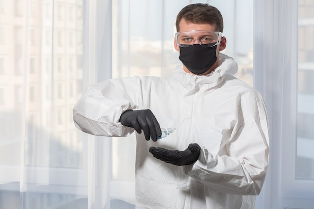 Doctor in ppe suit uniform and gloves treats hands with antiseptic. coronavirus outbreak. concept of covid-19 quarantine. doctor and medical care. personal protective equipment stop virus.