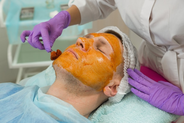 The doctor prepares the man's face for cosmetic surgery. treatment of the face with an antiseptic tank