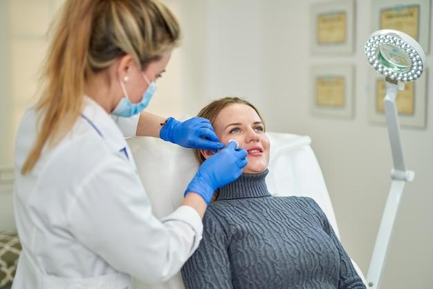 クリニックで美容整形のために女性患者を準備する医師