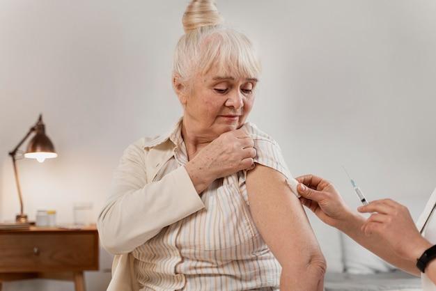 Доктор готовит вакцину для пожилой женщины