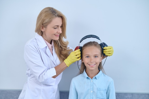 Doctor preparing a young patient for an audiometric test