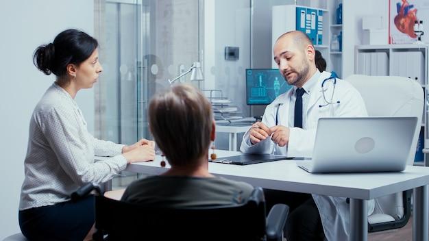 휠체어를 탄 노인 여성에게 치료를 처방하는 의사. dsabled 장애 장애인 노인 치료 현대 사립 병원 또는 클리닉. 의학 및 건강 관리 시스템