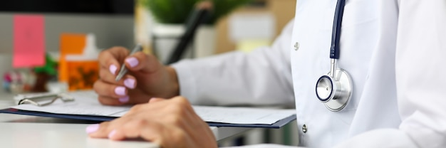 Doctor prescribing remedy sitting at working table