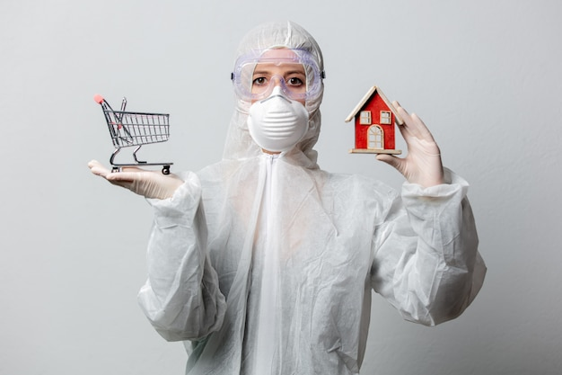 Doctor in protection clothes holds shopping cart and toy house, asking to stay at home