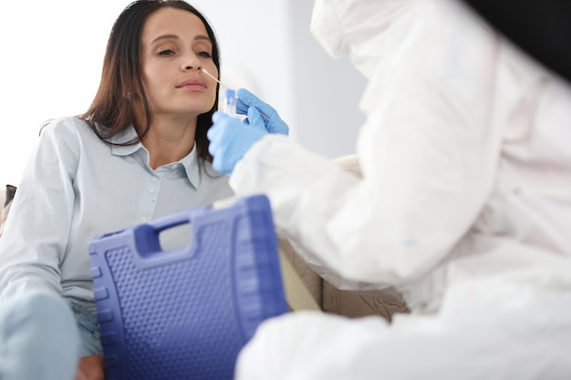 Doctor in protective antiplague overalls taking pcr swab from nose of woman patient at home