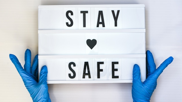 Doctor in protective gloves holding lightbox with text stay safe. back to school. social distancing. school quarantine concept. copy space. coronavirus second wave