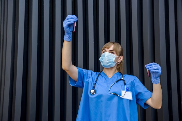 Doctor in protective gloves and mask holding red test tube on abstract background