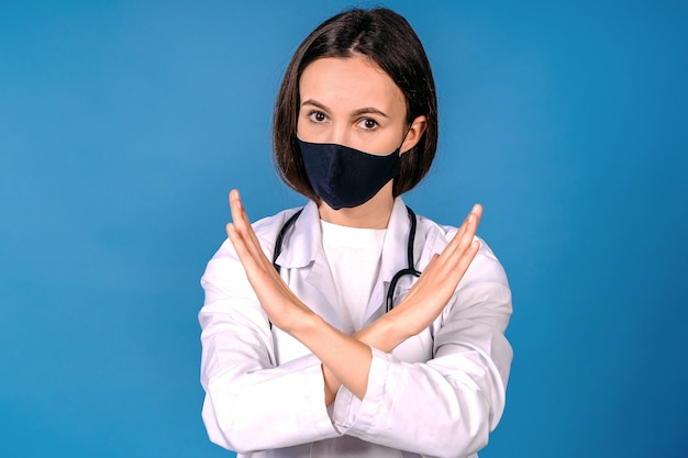 Doctor in protective mask showing stop gesture on blue wall. prevent spreading of coronavirus. female doctor hands showing crossed stop sign. doctor wearing mask stop coronavirus in fection