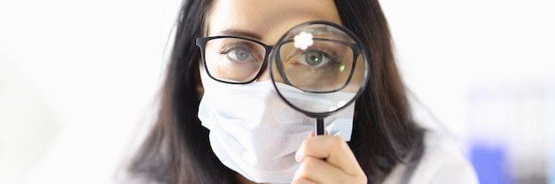 Doctor in protective medical mask looks through magnifying glass. search for medicinal products concept